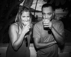 Smugly Sucking Suds at Duke's Barefoot Bar & Grill - Waikiki Beach (Oliver Leveritt) Tags: nikond7100 afsdxvrnikkor18200mmf3556gifed oliverleverittphotography hawaii oahu monochrome blackandwhite man girl drinking waikiki waikikibeach dukes