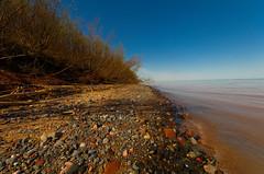 Shoreline (wackybadger) Tags: lake tree water rock wisconsin sand nikon stones shoreline greatlakes lakesuperior douglascounty wisconsinstatenaturalarea nikond7000 sigma1020mmf4exdchsm bearbeachsna sna402