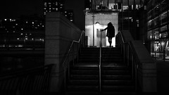 Girl going home at night - London, England - Black and white street photography (Giuseppe Milo (www.pixael.com)) Tags: england bridge unitedkingdom street city stairs contrast mysterious monochrome uk photography docks bw wallart geotagged white photo prints winter european streetphotography faceless canarywharf cold figure isleofdogs photograph fineart candid river print woman blackandwhite black europe urban horizontal onsale