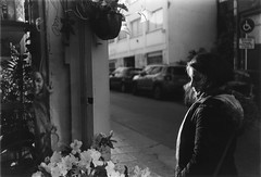 (intivisible) Tags: film 35mm analogic analog analógica blackandwhite blancoynegro byn bn bw monochrome chinon35fee girl chica mujer woman standing parada reflejo reflection vidriera window showcase florería flores flowers flowersshop contraluz backlight