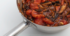 Pan with baked pieces of portobello mushrooms, sliced onions, olive oil, clove garlic, dried coriander, tobasco, Worcestershire sauce, black pepper, salt and tomatoes. (annick vanderschelden) Tags: worcestershiresauce bakedpieces blackpepper clovegarlic cooking culinary driedcoriander food greek mushrooms oliveoil pan portobello recipe salt slicedonions tobasco tomatoes