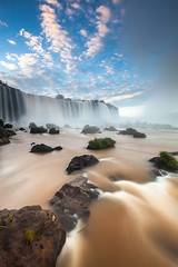 Iguazu Waterfall at Sunrise (baddoguy) Tags: arrival atmosphericmood blue brazil cloudsky colorimage flowingwater fozdoiguaçu iguacufalls iguacunationalpark large longexposure majestic morning motion nationalpark nature nopeople outdoors paranastate passion photography river sky southamerica sunlight sunrisedawn tourism travel traveldestinations tropicalrainforest unescoworldheritagesite unusualangle vertical water waterfall wet