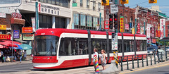 Toronto Transit Commission Bombardier Transportation Flexity Outlook streetcar in the city's Chinatown (edk7) Tags: auto city railroad urban woman toronto ontario canada building girl car sign shop architecture female store wire automobile chinatown ttc tram rail railway rr pole signage vehicle streetcar dundasstreet 2015 torontotransitcommission spadinaavenue rwy oldstructure scityscape 510spadina bombardiertransportation flexityoutlook edk7 olympuspenliteepl5