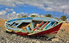 Theres a Hole In My Boat Dear Liza (tcees) Tags: rowingboat wreck shipwreck sky clouds beach palmtree lascaletas lanzarote canaryislands canaries