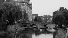 a leisurely stroll along the canal (lunaryuna) Tags: france lalsace strasbourg canal riverill bridge architecture trees urbanconstructs walk farewell blackwhite bw monochrome lunaryuna