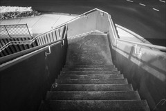 boronia-2176-ps-w (pw-pix) Tags: steps stairs rails railings bannisters shadows fence railing footpath road markings lines dashes steel hedge concrete wall ribbed textured corrugated parallel curved angles corner weathered aged dirty commercial retail shops evening ir infrared bw blackandwhite irmodifiednikon1v1 720nmir boroniamallshoppingcentre boronia easternsuburbs outereast melbourne victoria australia peterwilliams pwpix wwwpwpixstudio pwpixstudio