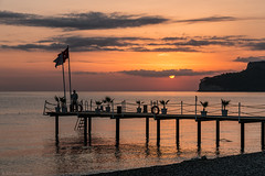 Watching as it begins again (Anthony Plancherel) Tags: kemer places seascape sunrise travel turkey turkiye sun sunlight sunglow sunrays clouds sky scatteredcloud orange gold purple pastelcolours pastels pier beach pebbles pebblebeach sea waves ripples reflection reflectedlight wood structure flags fence railing man person headland coastline coastal coast seashore seaside plants plantpots decorativeplants privatebeach tourist holidaymaker day beginning start dawn canon canon70d canon1585mm morning dawning early rise rising peaceful peace serenity serene tranquil tranquility shadow light lightandshadow sunset water outdoor shore landscape landscapephotography