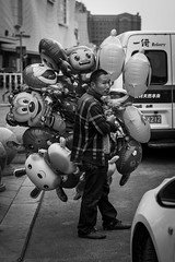 Selling happiness (Go-tea ) Tags: canon eos 100d 50mm bw bnw black white blackwhite blackandwhithe asia china yantai yantaishi shandongsheng chine cn street urban city asian chinese people portrait outside outdoor man alone seller balloons kids joy happiness fun fly flying air batch lot shirt cartoons characters famous business child children kid money life