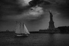 Gathering storm... (mehtasunil) Tags: nyc newyorkcity travel sunset sky blackandwhite storm water monochrome statue clouds sailboat river evening boat manhattan sony hudsonriver statueofliberty mate trielmar leicalens