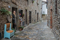 Looking Up (Erik Pronske) Tags: flowers dress italy montefioriali alley leadinglines tuscany seat up looking pot woman architecture black girl cobblestone business geramium italian montefioralle toscana it