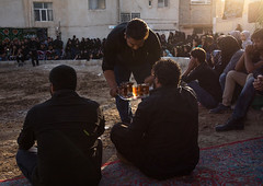 Iranian people drinking tea during a traditional religious theatre called tazieh about imam hussein death in kerbala, Isfahan province, Isfahan, Iran (Eric Lafforgue) Tags: 9people ashura ceremony colorimage commemoration esfahan historicalreenactment history horizontal imamhussein iran iranian isfahan islam ispahan largegroupofpeople men middleeast mourning muharram muslim nazri outdoors persia photography religion religiouscelebration shia shiism shiite tazieh theatre togetherness women isfahanprovince ir