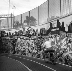2016246 (ruggeroranzani_RR) Tags: analog blackandwhite film 6x6 mediumformat rolleicordiv xenar3575 fomapan100 caffenolc graffiti man bicycle veneziamestre filmdev filmdev:recipe=11037 fomafomapan100 film:brand=foma film:name=fomafomapan100 film:iso=100 movement