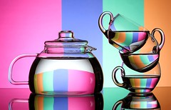 Psychedelic Tea (Karen_Chappell) Tags: tea teapot teacup glass pink blue green orange stack balance stilllife refraction reflection colourful colours colour multicoloured yellow topsy