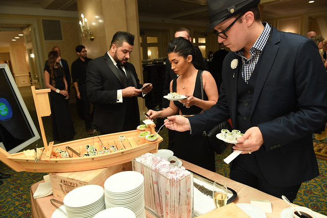 Arthur K of Fusion Events eating sushi at one of the food stations at the Top Choice Awards 2016