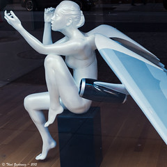 Unusual airframe (Thad Zajdowicz) Tags: street leica city travel blue urban sculpture woman color art window statue shop female angel digital nude square airplane wings outdoor pastel aviation advertisement airline unusual 1x1 airframe zajdowicz