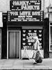 Northern Quarter #131 (Peter.Bartlett) Tags: manchester bag niksilverefex shopfront window unitedkingdom people urbanarte streetphotography olympuspenf lunaphoto walking shopwindow door facade peterbartlett car urban noiretblanc monochrome uk m43 woman text bw microfourthirds sign blackandwhite doorway city