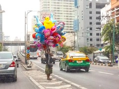 .  Maybe he doesn't know he fill the colorful moofd for big city under grey cloud sky (Araleya) Tags: life street square thailand happy colorful bangkok balloon squareformat   iphoneography  instagramapp uploaded:by=instagram