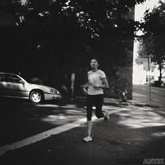 Jellyfish Can Fly (obscurantik) Tags: street city urban blackandwhite woman blur blancoynegro monochrome oregon portland nikon downtown streetphotography running creativecommons runner parkblocks focalblur nikon1j2