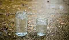 Measuring the Rain (UniquelyHis4ever) Tags: rain water rainyday masonjar waterdrop splash raindrop sidewalk jar cup waterbottle