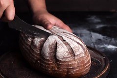 Close-up of baker hands cutting fresh bread from oven (lyule4ik) Tags: bread food slice healthy bakery baker meal fresh cook cutting flour female woman knife board nutrition cut wooden loaf rustic chef warm preparation traditional taste bake professional quality work seeds bakehouse flavor commercial occupation handcraft culinary tradition manufacturing oven ingredient menu industry product baked black breakfast brown caucasian