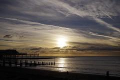 pier into the setting sun (Sundornvic) Tags: aberystwyth wales beach sea sky sun sunset clouds blue white glow pier jetty waves ripples rocks