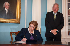Counselor of the Department Tom Shannon looks on as Sheila Gwaltney signs her appointment papers to become the U.S. Ambassador to Kyrgyzstan at the U.S. Department of State in Washington, D.C., on August 20, 2015. [State Department photo/ Public Domain]