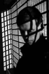 Edgar / Edmire. DJ (Pim Geerts) Tags: shadow portrait blackandwhite bw white man black male netherlands monochrome lines zeiss canon grid eos graphics artist dj zwartwit nederland 85mm carl rooster unusual portret producer schaduw zwart wit raster ze planar lijnen 1485 grafisch artiest 5dm2