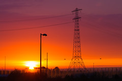 Power Tower at Sunrise (Borut Slabe) Tags: red sky orange sun holland netherlands amsterdam clouds sunrise streetlight outdoor cable serenity powerline plain lightpole powertower