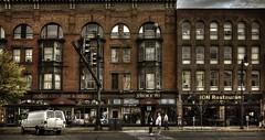 Survival of the Fittest (Jon Scherff) Tags: buildings oldbuildings brickbuildings street streetphotography nikond810 35mm people storefront peoplewatching bricks sidewalk storefronts mainstreet nikonafsnikkor35mmf14g