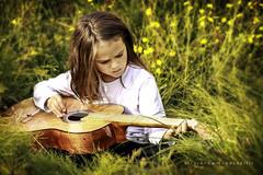The Guitar Player (Sigrun Saemundsdottir) Tags: child children kid kids youth young guitar nature outdoor playing music musicplayer guitarplayer childplayingguitar boywithlongher boy grass reeds environmentalportrait sigrunsaemundsdottirphotography portrait beauty beautiful sweet musician yellow longhair