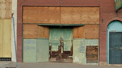 Boarded-up storefront - Erie Street, Lowell district, Bisbee, Arizona (edk7) Tags: nikond3200 edk7 2013 us usa arizona cochisecounty bisbee lowell ghosttownheritagedistrict old vintage classic architecture building oldstructure city cityscape urban store boardedupstorefront shop brick plywood arch door weatheredwood