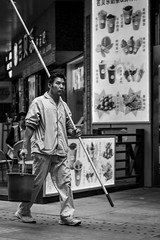The window cleaner (Go-tea ) Tags: canon eos 100d 50mm bw bnw black white blackwhite blackandwhithe yantaishi shandongsheng chine cn asia china yantai street urban city asian chinese people portrait outside outdoor man alone windows cleaner stick pot water heavy walking walk unifrom dirty dirt long carry carried shoulder hand hands pole perch rod