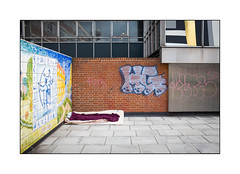 Homeless Man's Pitch, East London, England. (Joseph O'Malley64) Tags: homeless homelessness sleepingpitch homelessinlondon eastlondon eastend london england uk britain british greatbritain wall walls handpaintedtiles tiling brickwork pointing corrugatedsteelpanels windows aluminiunframes paving pavement officeblock bedding roughsleeping sleepingrough bereft graffiti throwies tags capitalcity city