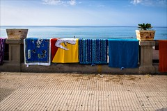 PA136816 Italy Sicily Cefalu (Dave Curtis) Tags: 2013 cefalu em5 europe italy omd olympus sicily beach towels promenade stall