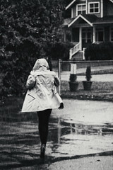 Under the Weather ) (Natalia Medd) Tags: rain weather girl running people street house fence puddle autumn fall september bw blackandwhite monochrome mono