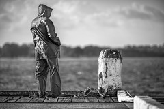 The fisherman (Chas56) Tags: fishing fisherman thefisherman bw blackandwhite pier jetty sea seaside canon canon5dmkiii candid person people monochrome black white raincoat weather protection solitude alone elements theelements dof depthoffield