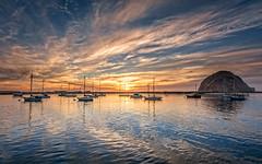 The Siren's Call (Calpastor) Tags: sea ocean coast bay harbor sunset night sky sun clouds blue orange water boats ship dingy yacht california morro rock