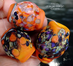 Rocks Orange Mango Queens (Laura Blanck Openstudio) Tags: openstudio openstudiobeads handmade glass lampwork beads bead set jewelry rocks nuggets faceted big whimsical funky odd speckles murano colorful multicolor abstract asymmetric organic art fine arts artist artisan made usa frosted matte etched opaque winner show festival published violet lavender lilac purple grape mango orange coral ocher maize enamel white eggplant copper green