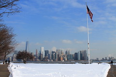 Liberty (courtneymartin-luce) Tags: libertyisland newyork america usa snow clear sky blue flag pole buildings architecture nature constructed trees