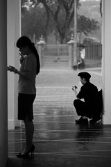 In each of our own world (ah.b|ack) Tags: street bw rain zeiss stand singapore bokeh sony smoking crouch handphone 135mm wideopen f35 sonnar czj a7ii carlzeissjenaddrmcs135mmf35 a7mk2