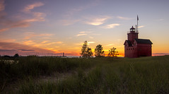 August Sunset (Kevin Povenz) Tags: blue sunset sky lighthouse holland beach water grass yellow landscape evening dusk michigan flag ottawa august lakemichigan bigred hollandstatepark westmichigan 2015 ottawacounty sigma1020 canon60d kevinpovenz