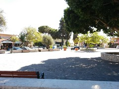 (Psinthos.Net) Tags:  psinthos village square psinthossquare psinthosvillage    villagecenter      stonewall pavement     cars day sunnyday light sunlight     shadow  pots   olivetrees  trees planetree   treebranches  bench benches    pinetree    cypresstree church  houses  noon    autumn october