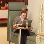 A student typing a paper in the library.