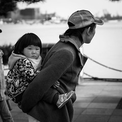 Backpack (Go-tea 郭天) Tags: qingdaoshi shandongsheng chine cn canon eos 100d street urban city qingdao china asia asian chinese people outside outdoor monochrome bw bnw black white blackwhite blackandwhithe old woman young kid girl child grandma granny daughter back carried carrying carry hat cap cold coat cute lovely little beautiful backside backpack funny lucky family together relax heavy difficult difficulty walking walk portrait grandchild grandmother