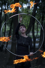 Planning ahead (A><EL) Tags: fire juggler juggling flame portrait hoop hulahoop performance girl female woman circus canon 50mm outdoor brunette