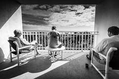 Outlook (clive_metcalfe) Tags: ocean people shadows balcony resting view clouds sky chair table