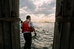 Liberty (reinfected) Tags: life street new wood york city nyc sunset man men water statue clouds liberty photography evening photo waves looking metro candid sony working cities logs metropolis ripples 20mm vest a6000