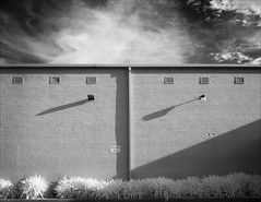 boronia-2187-ps-w (pw-pix) Tags: wall lights shadows symmetry assymetry vents downpipe gutter sign gym gymparkingonly plants agapanthus kerb sky clouds commercial evening ir infrared bw blackandwhite irmodifiednikon1v1 720nmir ericaavenue boronia easternsuburbs outereast melbourne victoria australia peterwilliams pwpix wwwpwpixstudio pwpixstudio