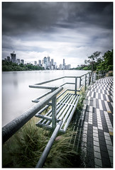 Bench along Brisbane river (JakaPH Photography) Tags: city cityscape skyline brisbane queensland australia clouds cloudy river rivercity water movement motion long exposure landscape looking lee little stopper nd 6 10 16 walkway street colour color bench sky skyscraper buildings day daylight travel destination desaturated