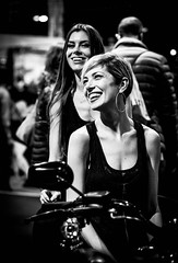 With Or Without You (lothar1908) Tags: ragazze girls smile moto bw biancoenero blackandwhite sorriso blondebrune scollatura dcollet interno indoor canoneos5dmarkiii ef70200mmf28lisiiusm eicma orecchini canottiera ridendo bn candid istantanea canottiere outfit street